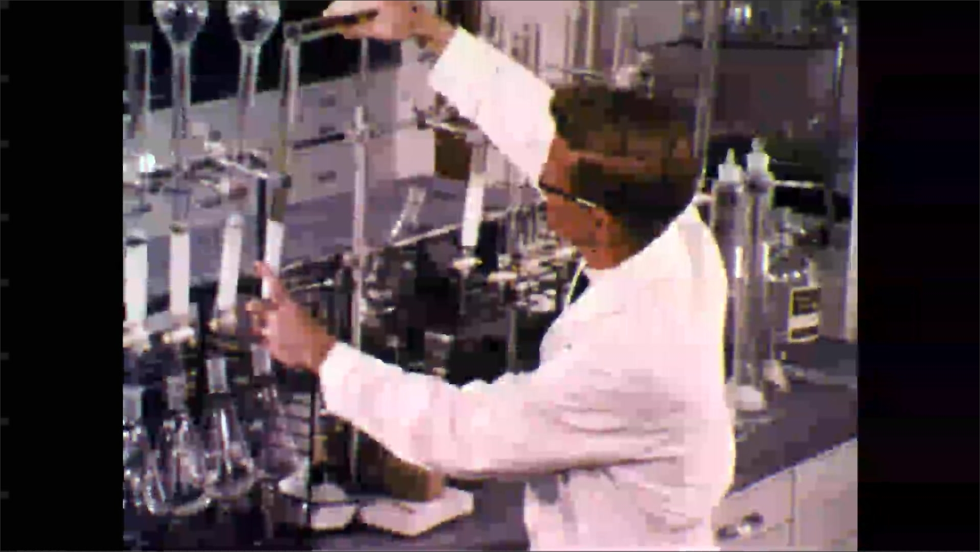 1960s: Chemistry lab, racks of glassware, man in lab coat pours liquid into glass column, removes flask.