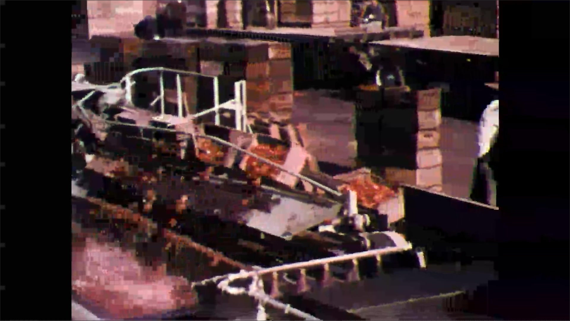 1960s: Industrial food processing plant, stacked wooden pallets, crates of tomatoes travel down line, are dumped into water trough. Men move crates. Rollers move tomatoes into water.