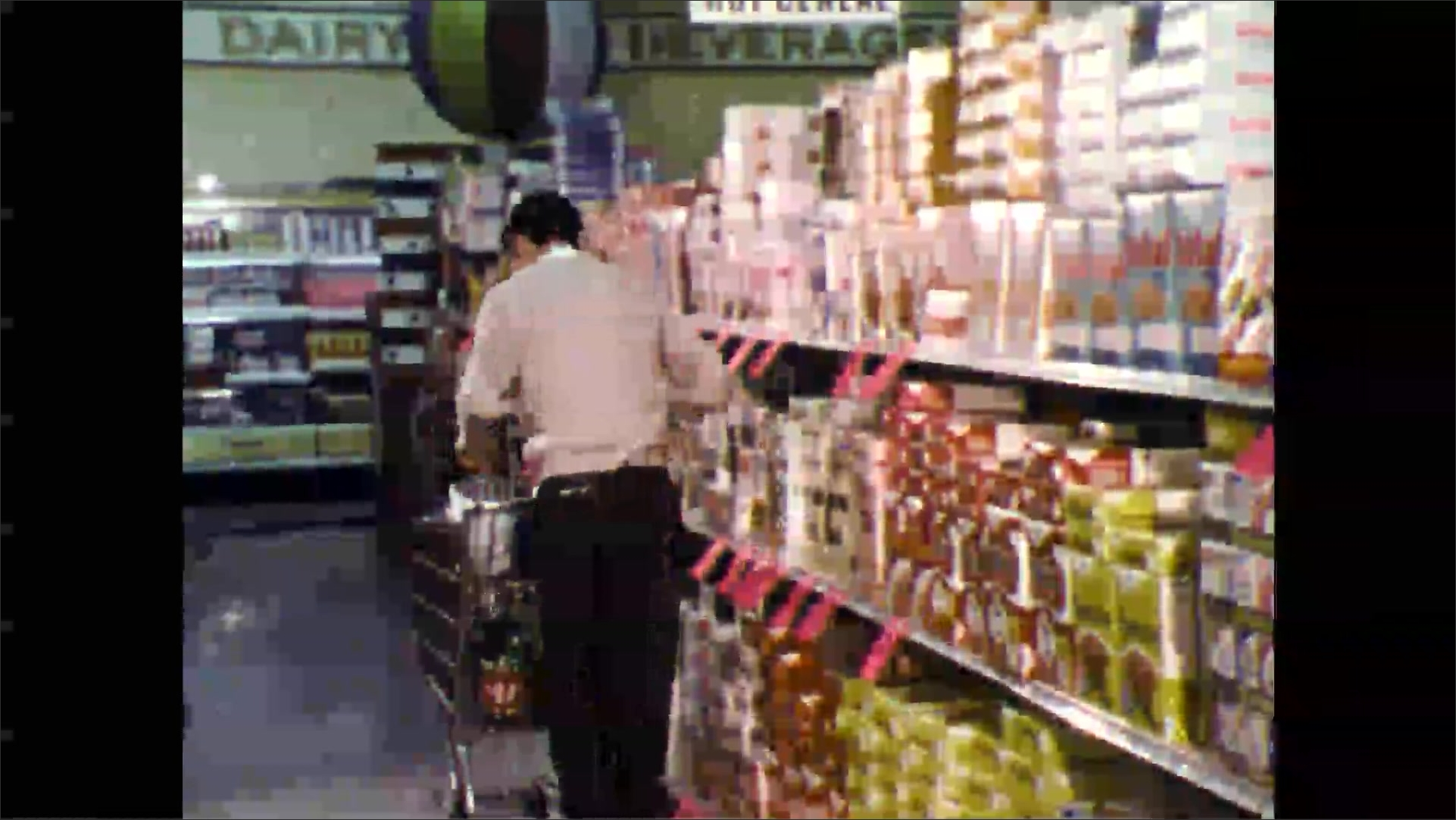 1960s: Grocery store, young man pulls boxes off shelf, places in shopping cart, pulls can off shelf.