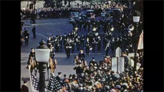 1940s: Large crowd of people line the streets for parade. Police on horseback followed by marching band. Capitol building in the background.