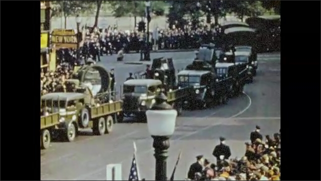 1940s: Jeeps go down street in large parade. Jeeps are followed by military trucks followed by pick-ups with officers in them.