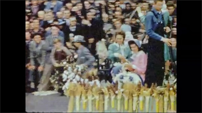 1940s: Large crowd of people in stands, watching float go by in parade. Woman in center of flower on float. Title card: Georgia Shows Its Stuff. Peach float. Cotton gin float.