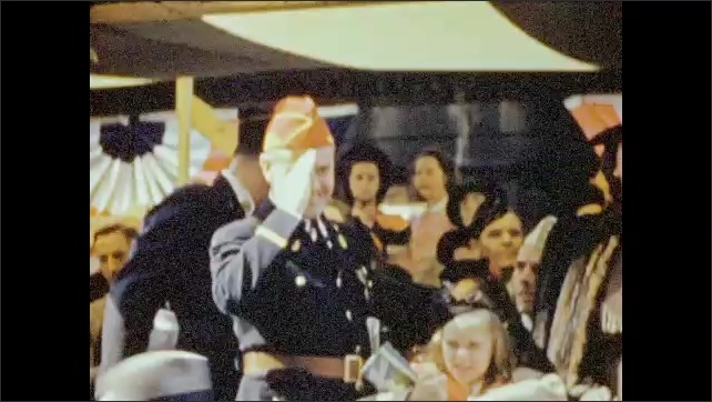 1940s: People in uniform and dress watching parade. Retired men in uniform march in parade and salute. Officer salutes them back. Title card: Man-Mountain Dean… Man in uniform. Woman on float.