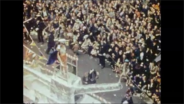 1940s: Majorette leads marching band in parade. Float shaped like a battleship goes by. Marching band in parade.