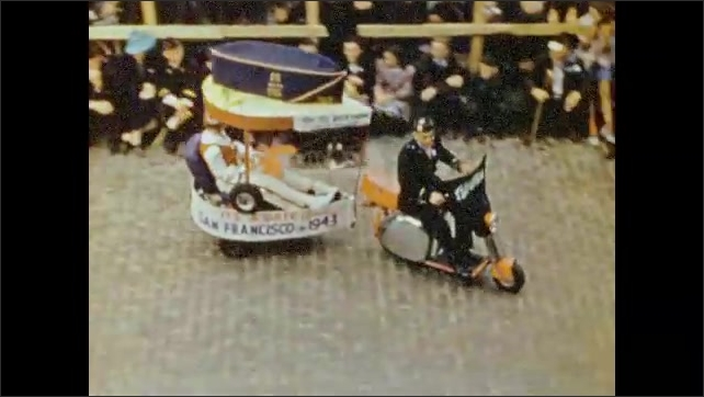 1940s: Marching band goes by in parade. Man walks through parade holding sign. Man on scooter pulls small float. Locomotive engine float. Majorette in parade. Two majorettes lead marching band.