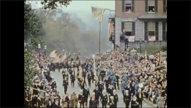 1940s: Marching band goes by in parade. Men march in uniforms. Line of majorettes. Float shaped like a locomotive pulls a trailer with people in it through parade.