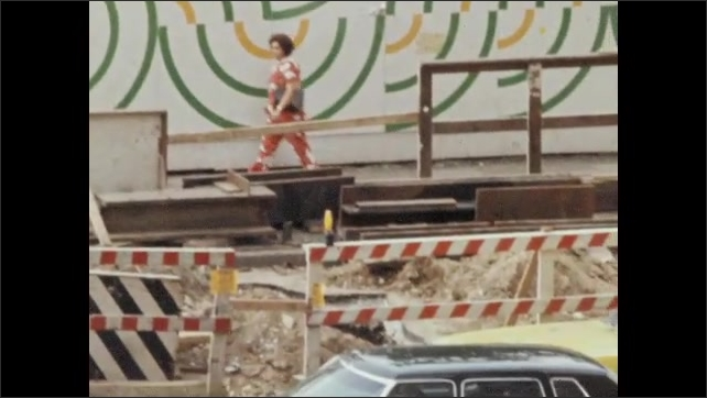 1970s: People walk near sidewalk construction and mural in city. People wait on corner by barricade to cross city street.