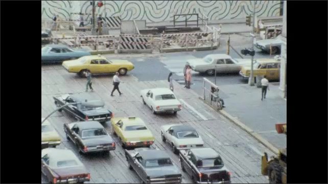 1970s: People and traffic navigate busy city streets near painted mural. People cross between traffic on busy city street.