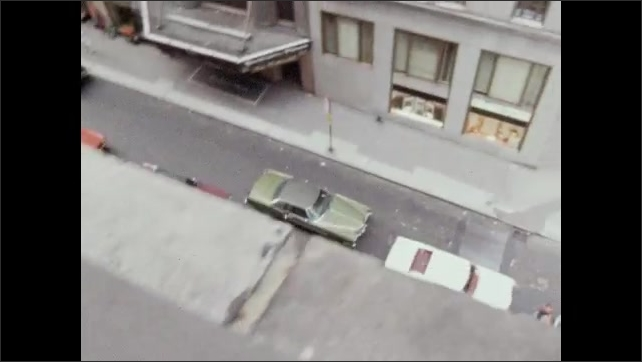 1970s: Wires and camera equipment on window sill. Cars parked in alley between city buildings. Text on paper taped to wall. Film camera on tripod.