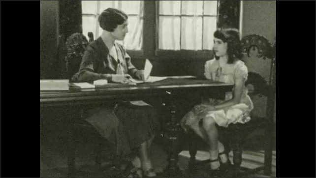 1930s: Woman is seated at long, formal desk. Girl sits at end of desk listening as woman speaks. Woman speaks to girl and girl responds.