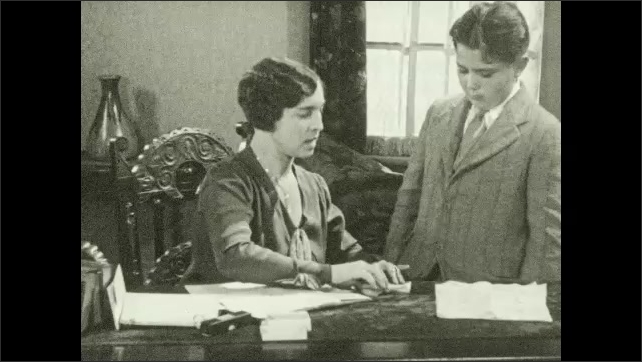 1930s: Woman seated at desk unfolds and tears center out of papers as boy in suit watches.