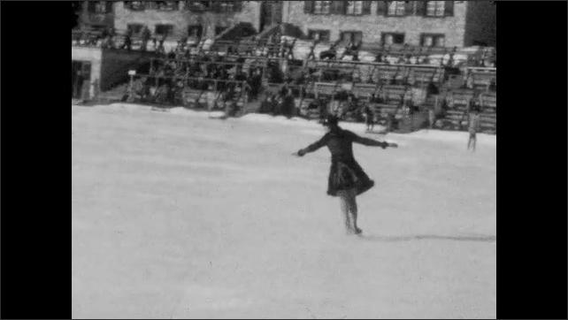 1940s: Long shot of woman skating. Woman skating on ice rink.