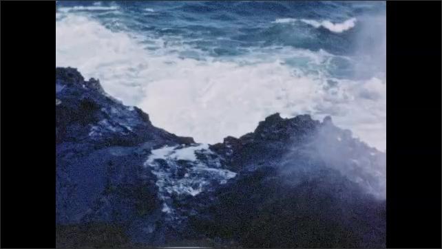 1940s: Waves crash on rocks.  People stand on observation deck.