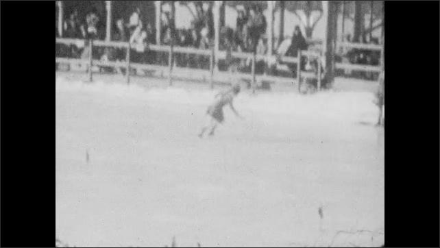 1940s: Long shot, woman skating on ice rink.