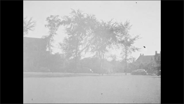 1940s: Pan across field, bulding exterior.