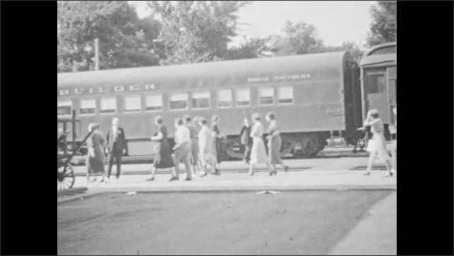 1940s: Tracking shot, Factory building. Sign at train station, tilt down, pan to train. People next to train car. Sign at train station.