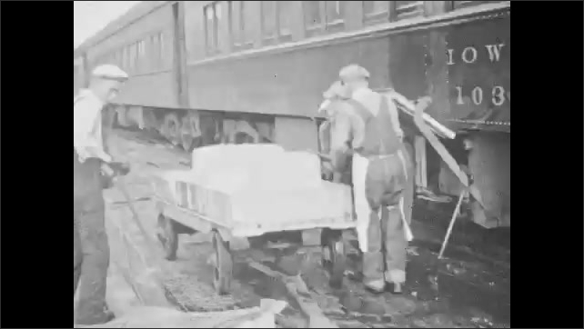 1940s: Man throws bags to man on top of train, pan across men working. Men pull cart next to train. People on sidewalk, tilt up to sign on building.