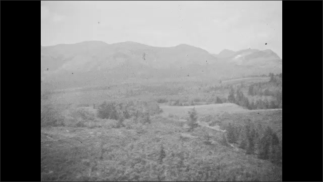 1940s: Tracking shot from train, high angle view of river, pan across trees.