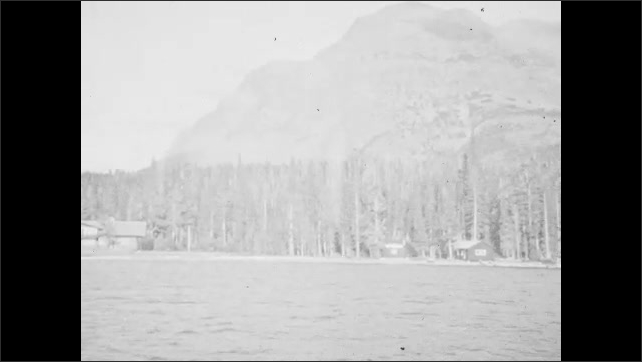 1940s: UNITED STATES: view across lake. Building by lake. Boat trip on lake. Forest by lake and mountains. Snow covered mountain
