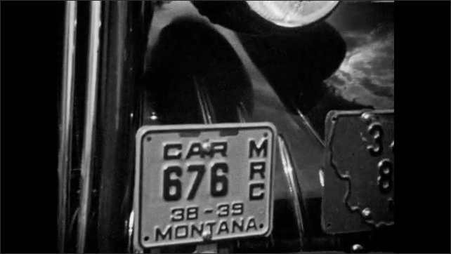 1940s: UNITED STATES: man stands by car. Alberta number plate on car. Montana number plate. View across valley towards mountains. Grill on front of car.