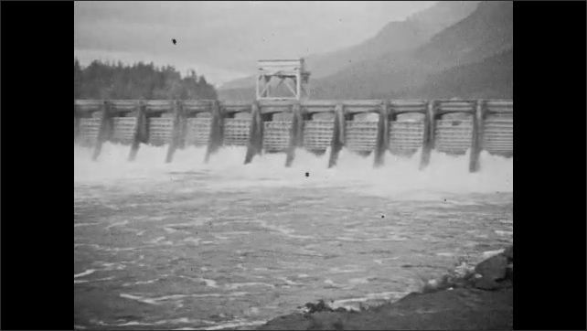 1940s: CANADA: Bonneville Dam visit. People feed ducks on pond. View across dam. Man smokes by dam. Man draws picture by water