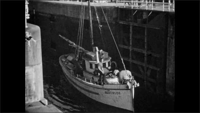 1940s: CANADA: lock gates open. Boat leaves lock. Gertrude boat. Boats leave through lock gate. Lock keeper carries rope from boat.