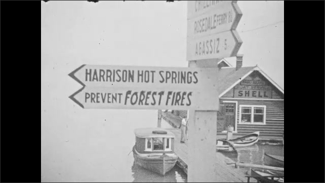 1940s: CANADA: totenpole from bottom to top. Passengers climb down from train. Harrison Hot Springs sign. Prevent Forest Fires sign.