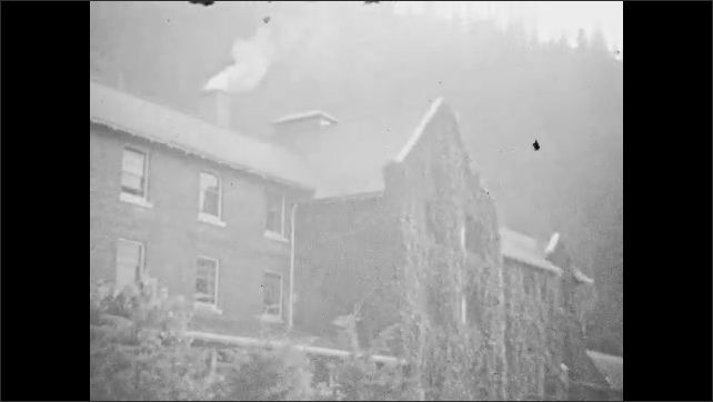 1940s: CANADA: visitors arrive at hotel. Smoke from chimney of house. Hot Springs Water sign.