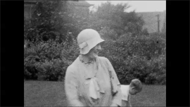 1940s: UNITED STATES: guests arrive at garden party. Lady talks to cameraman. Ladies in garden. Ladies smile at camera