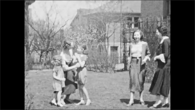 1940s: UNITED STATES: lady in doorway of house. Small child in garden. Lady kisses girl. Ladies and children in garden