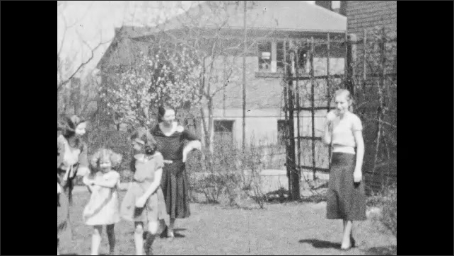 1940s: UNITED STATES: lady catches girl in garden. Ladies and girls in garden. Ladies laugh in front of camera