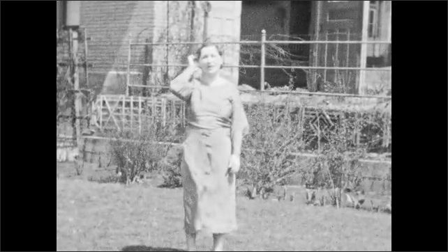 1940s: UNITED STATES: lady hugs girl in garden. Ladies chase girls in garden. Lady looks at camera. Lady in scout uniform in garden
