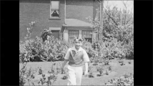 1940s: Boy hides in bushes and walks around in yard.  Boy points and speaks.