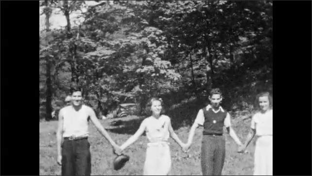 1940s: Crowd of people talk.  Teenagers hold hands in circle.