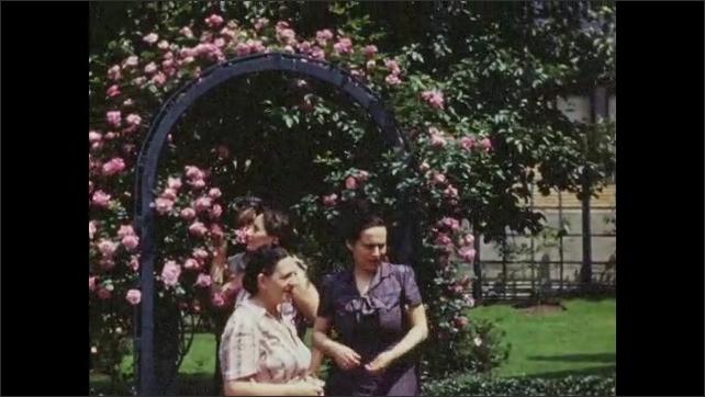 1940s: Group of women stand near arbor covered in flowers.  Woman tucks flower behind ear.  Women wave.  Women walk.