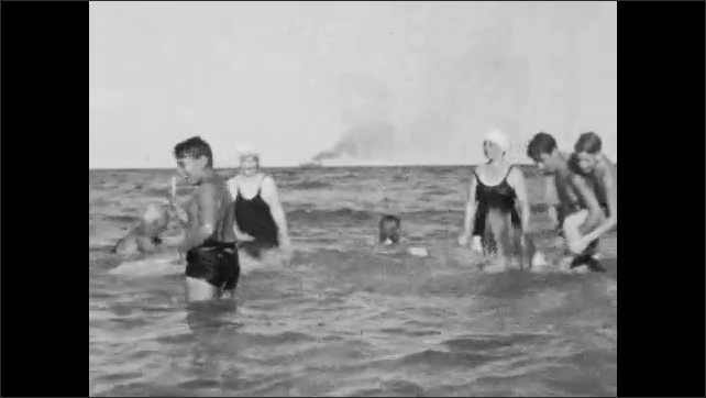 1940s: People splash and play in the ocean.