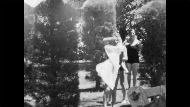 1940s: Family sits on beach.  Family walks down sidewalk.
