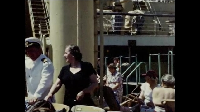 1950s: Woman walks behind deck chairs on cruise ship. Woman talks to man in uniform.