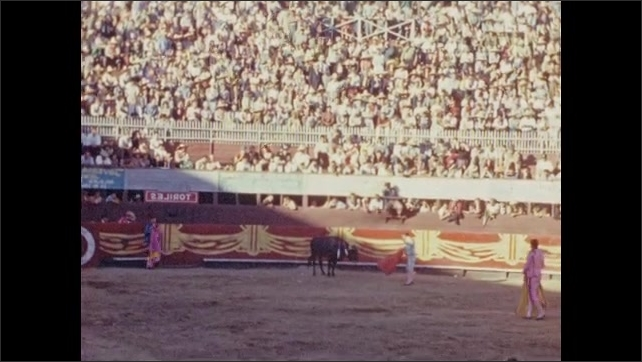 1940s: Men taunt bull with capes. Crowd stands up, cheers. Man stabs bull.