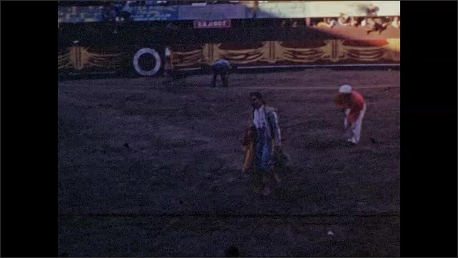 1940s: Matador walks away from ring. Men on horse poke at bull. Men taunt bull with capes and sticks.