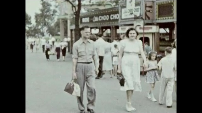 1940s: Men, women, and children walk around outside.