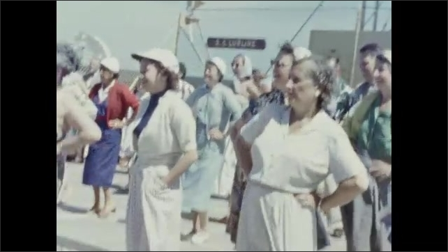 1950s: Women dance back and forth with hands on hips, swaying. Man walks across deck of ship and points. Man dances with hands on hips.