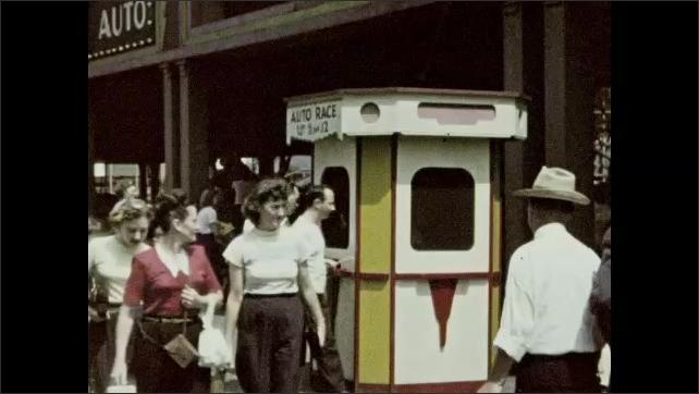 1940s: Men, women, and children walk around outside. Men buy tickets at booth.