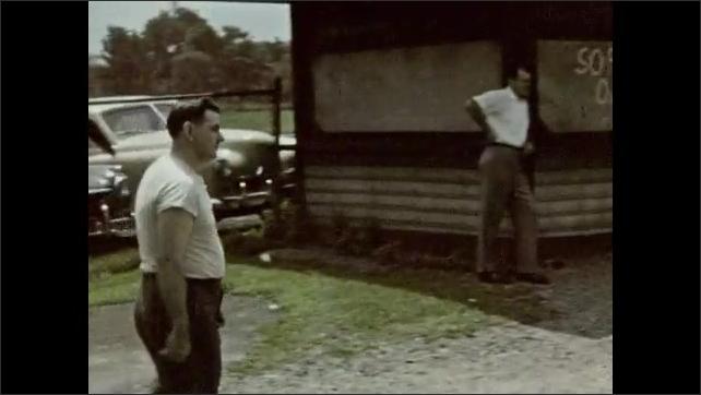 1940s: Man walks across field. Men throw ball back and forth. Men play baseball.