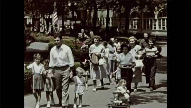 1940s: Man stands outside, holds purse, poses. Men, women, and children walk around outside.