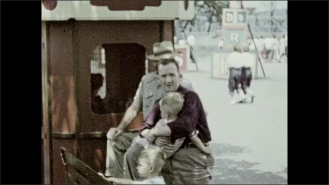 1940s: Men, women, and children walk around outside, man waves. Man holds child. Couple sits on bench.