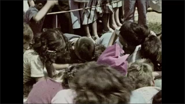 1940s: Children stand together. Children pile on top of each other, parents watch.