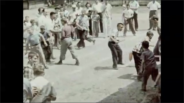 1940s: Men, women, and children stand and watch. Man directs boys holding sticks. Boys sword fight with sticks, try to hit balloons tied on belts.