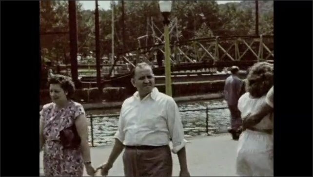 1940s: Men, women, and children walk around outside. Woman smiles and talks. Couple holds hands, man holds baby.