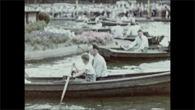 1940s: People row boats on lake. Men, women, and children walk around outside.